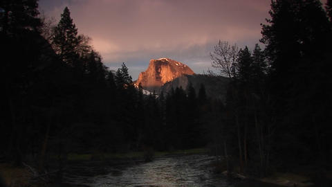 Medium shot of flowing Merced River with radiant Half Dome of Yosemite National Park centered in the Footage