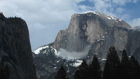 Medium wide shot of Yosemite's Half Dome hosting clouds and winter snow Footage