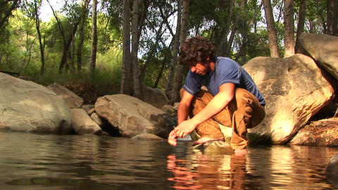 Low-angle of a hiker washing his face in a mountain pool Stock Video Footage