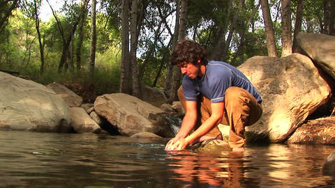 Low-angle of a hiker washing his face in a mountain pool Footage