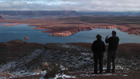 Medium-shot of a couple standing on a snow-dusted area looking over Lake Powell, Arizona Footage