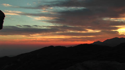 Pan-right of a fiery California sunset to a rock-climber... Stock Video Footage