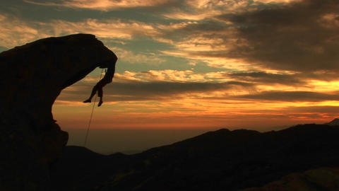 Medium-shot of a rock-climber silhouetted by the setting California sun Footage