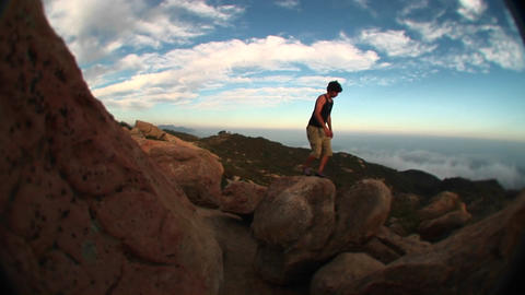 Fish-eye of a young hiker hopping from boulder to boulder in the Santa Barbara Mountains Footage