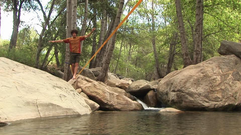 Medium-shot of a young man slacklining across a swimming... Stock Video Footage