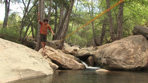 Medium-shot of a young man slacklining across a swimming hole Footage