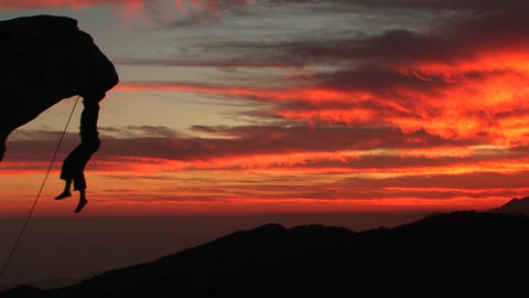 Medium-shot of a rock-climber silhouetted by a fiery California setting-sun Footage