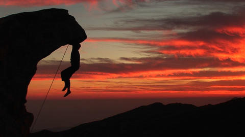 Medium-shot of a rock-climber silhouetted by a fiery... Stock Video Footage