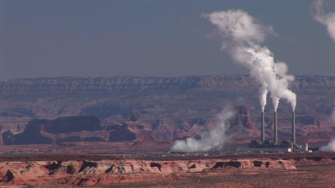 Medium-shot of a factory in the Arizona Desert emitting pollution Footage