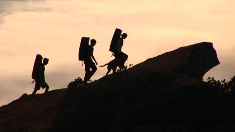 Medium-shot of a group of silhouetted backpackers and a dog climbing a rock structure Footage