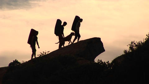 Medium-shot of a group of silhouetted backpackers and a... Stock Video Footage