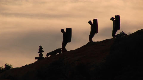 Pan-left of three back-packers and a dog silhouetted against an evening sky Footage