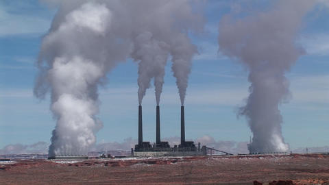 Medium-shot of a factory in the Arizona desert, belching polluting fumes into the air Live Action