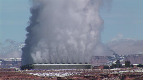 Medium-shot of a factory in the Arizona Desert emitting clouds of smoke Footage
