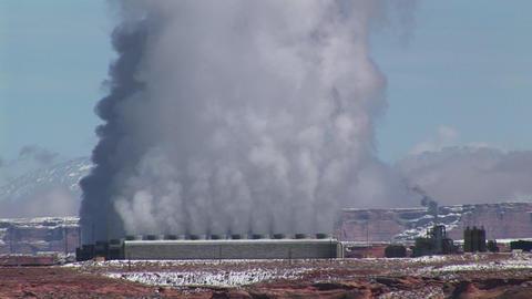 Medium-shot of a factory in the Arizona Desert emitting clouds of smoke Footage