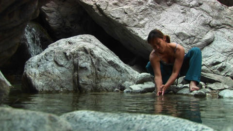 Medium shot of a woman rock-climber washing her hands in... Stock Video Footage