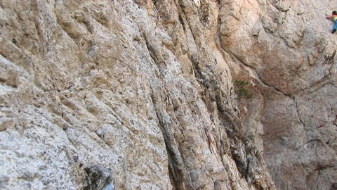 Pan-right of a rock-climber laboriously climbing a... Stock Video Footage