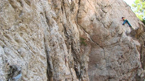 Pan-right of a rock-climber laboriously climbing a granite rock-face Footage