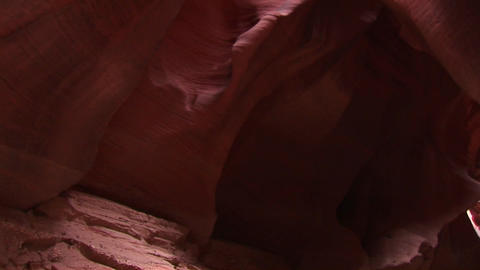 Tilt-up of a rock-climber making her way up a sheer rock-face Live Action