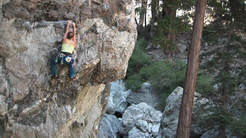 Pan-up of a rock climber making her way up a... Stock Video Footage