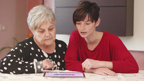 generations compared: young woman explains to her grandmother tablet technology Live Action
