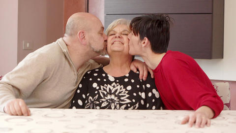 smiling grandmother kissed by her grandchildren Footage