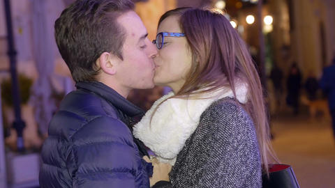 young couple in cheerful mood in the public way, smiles, kiss, hugs Footage