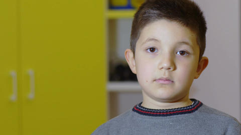 portrait of a little boy looking in front of him, mouth closed, eyes opened Footage