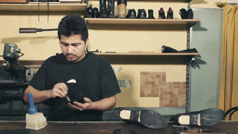 craftsman brushing a rubber sole for a pair of boots with glue Footage