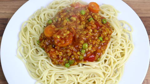 Serving A Red Lentil Vegan Bolognaise On To a Bed Of Spaghetti Live Action