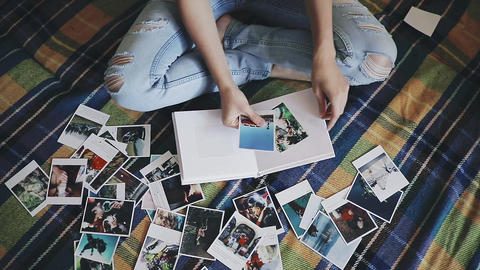 Woman looking at photos and creating an album Live Action