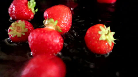 Strawberries Falling Into Shallow Water With A Black Backdrop Live Action