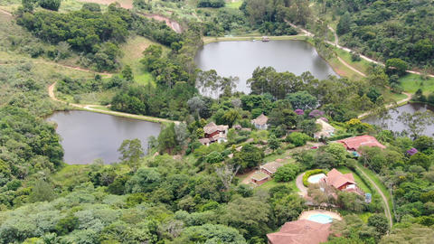 Aerial view of valley with lake, forest and villa in tropical country Live Action