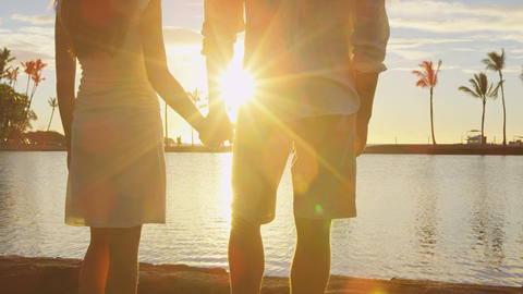Romantic couple at sunset holding hands at beach watching the sun set vacation Live Action