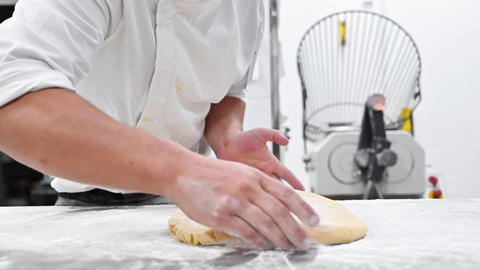 Chef kneading dough at commercial kitchen. Pastry Chef hands kneading dough on Live Action