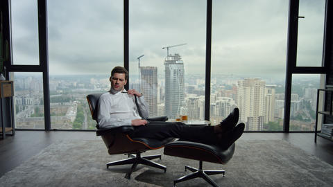 Businessman relaxing in office chair. Exhausted employee adjusting tie in office Live Action