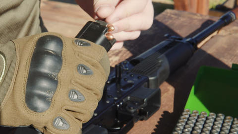 Loading a gun magazine with bullets Live Action