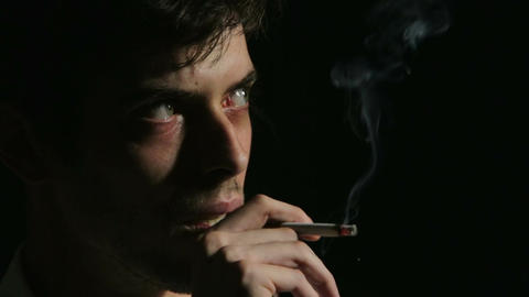 desperate young man on dark background: sad, sadness, smoking, loneliness Footage