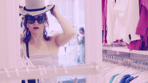 beautiful woman is searching for a hat: woman trying a hat Footage