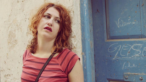 thoughtful red haired woman: pensive girl leaning against the wall Footage