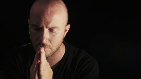 young man prays intensely black background, religion,… Stock Video Footage