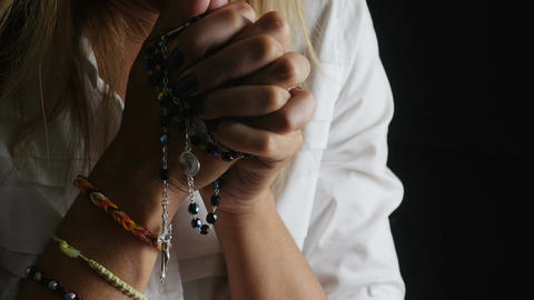 woman is praying on dark background with rosary beads: cross, religion, God Footage