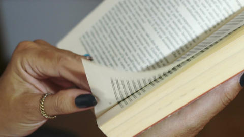 close up on hands of woman reading a book Footage