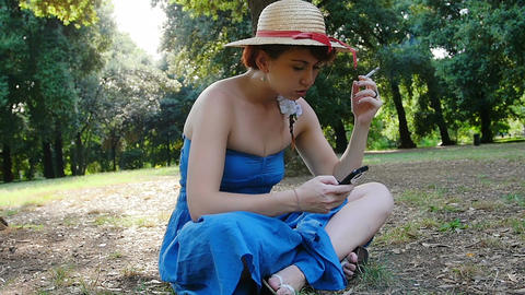 young woman smokes and read news and messages on her mobile phone Live Action