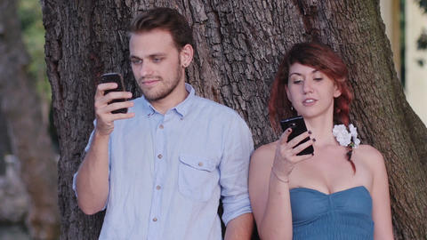 a couple using smart phones near a tree in a park Filmmaterial