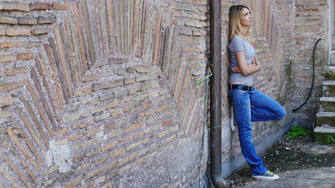 Bored and lonely girl leaning against a wall: sad, sadness, thoughtful Live Action