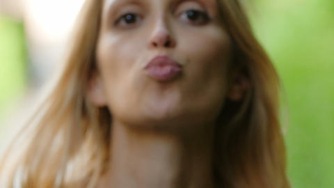 young pretty girl gives a kiss to the camera: love, sensual, smile, slow motion Footage