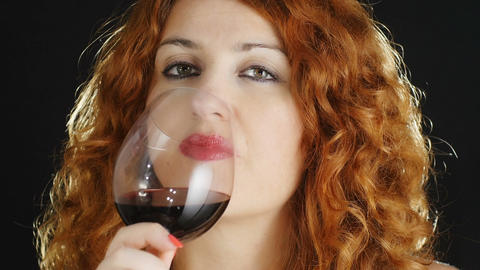 young woman tasting red wine: drinking red wine in a goblet glass Footage