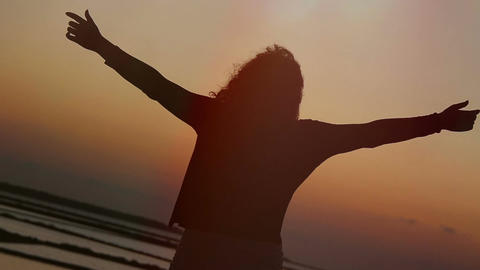 woman contemplates the sky at the sunset and opens her arms: freedom, well-being Footage