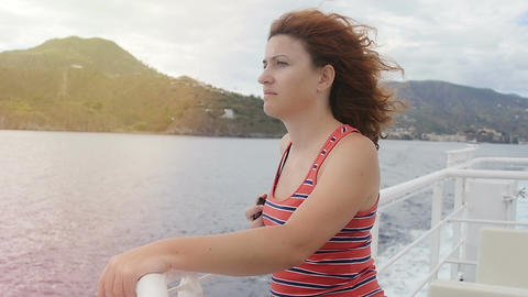 young pensive woman looking at the sea aboard of a ship: summer, sun, wind Footage